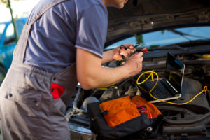 Professional car mechanic working in auto repair service, using